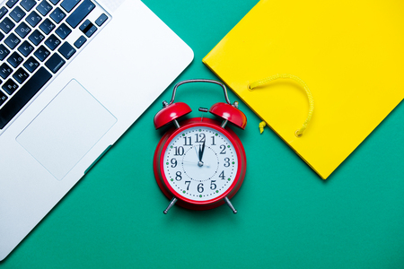 buying time: beautiful yellow shopping bag, cute alarm clock and modern silver laptop on the wonderful blue background