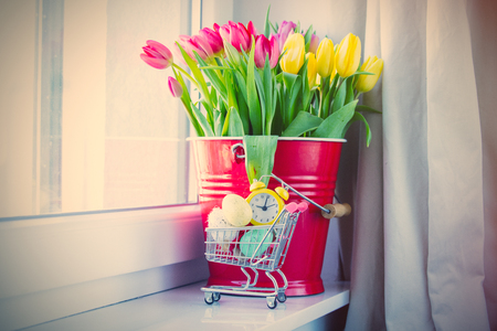 bunch of beautiful colorful tulips in red bucket, alarm clock and easter eggs in shopping cart on the wonderful windowsill Stock Photo
