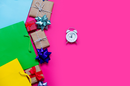 buying time: beautiful small gifts, bows, alarm clock and colorful cool shopping bags on the wonderful pink background