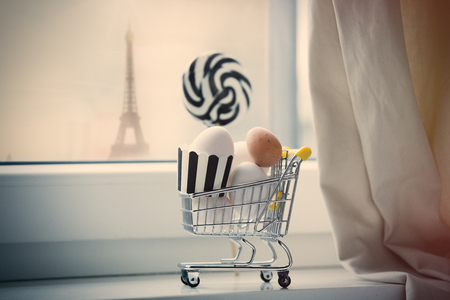 seasonable: beautiful easter eggs in cool shopping cart  and lolipop shaped toy on the wonderful white windowsill