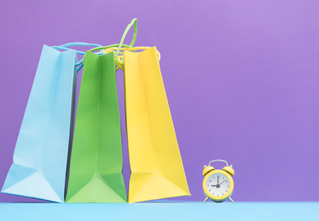 buying time: cute small alarm clock and shopping bags on the wonderful purple background