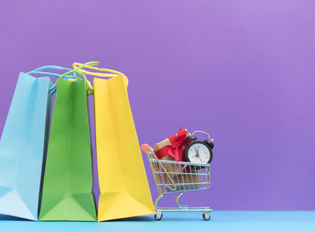 buying time: cute small gifts and alarm clock in the cool shopping cart and shopping bags on the wonderful purple background Stock Photo