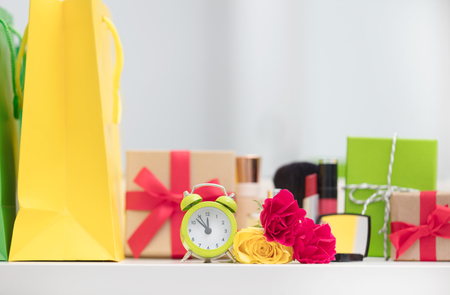 cute shopping bags, make up set, gifts, alarm clock and roses on the wonderful mirror background