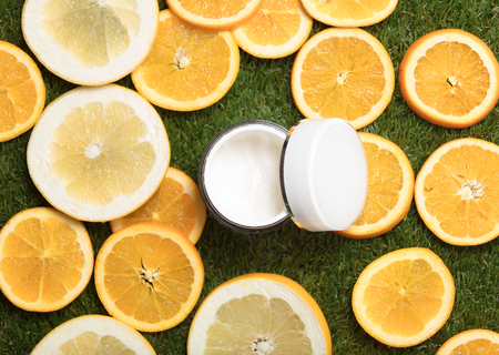 photo of opened cream near dried orange slices on the wonderful green grass background