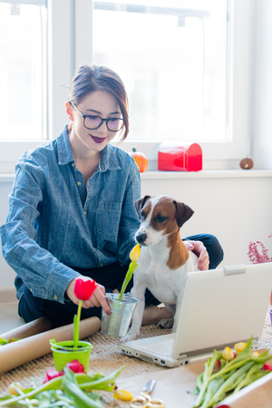 young woman holding pot with flower near laptop, dog and things for wrapping tulips on the floor Stock Photo