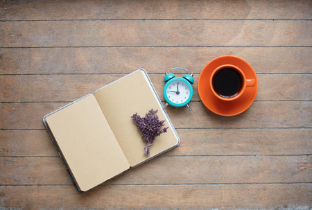 photo of opened notebook, bunch of lavender, alarm clock and cup of coffee on the wonderful wooden brown background Stock Photo