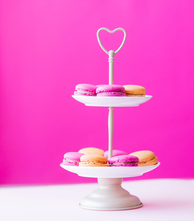 heart shaped: photo of beautiful stand full of colorful macaroons on the wonderful pink studio background