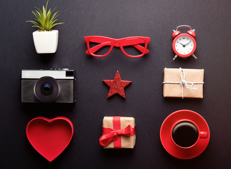 heart shaped: photo of alarm clock, glasses, plant in pot, star shaped toy, alarm clock, retro camera, cup of coffee and cute gifts on the wonderful black studio background