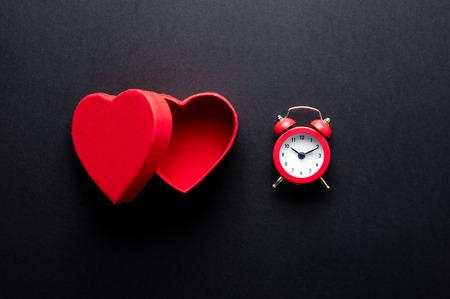 heart shaped: photo of beautiful cute heart shaped box and alarm clock on the wonderful black studio background Stock Photo