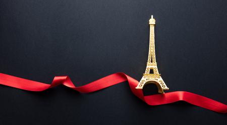 photo of beautiful Eiffel Tower shaped souvenir and ribbon on the wonderful black studio background
