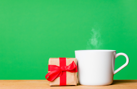 photo of beautiful gift and cup of fresh coffee on the wonderful green studio background