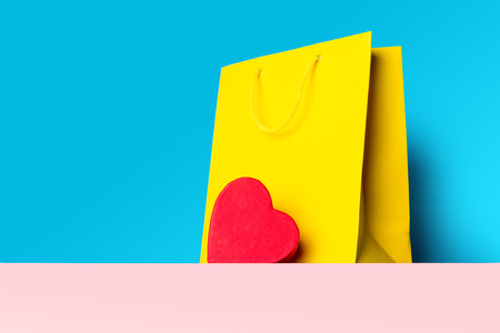 heart shaped: photo of shopping bag and heart shaped toy on the wonderful blue studio background Stock Photo