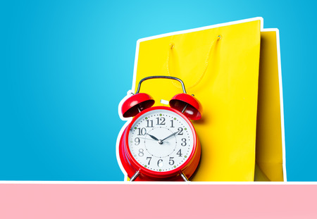 buying time: photo of shopping bag and alarm clock on the wonderful blue studio background
