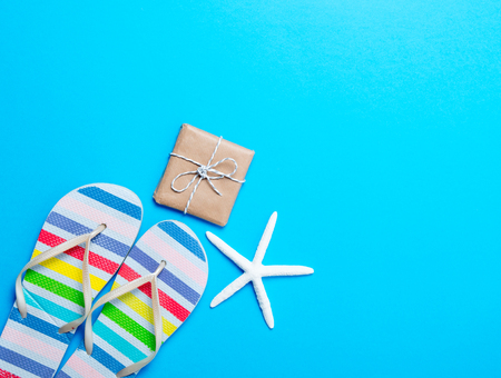 photo of colorful sandals, gift and dried starfish on the wonderful blue studio background