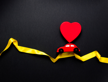 Little toy car with heart shape box moving over twisted ribbon on black background