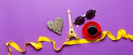 Cup of coffee and Eiffel tower toy with sunglasses on purple background