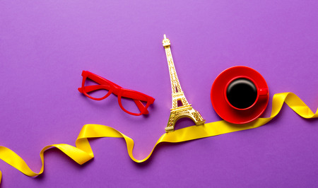 Cup of coffee and Eiffel tower toy with glasses on purple background Stock Photo