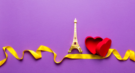 Heart shape box and Eiffel tower toy with ribbon on purple background