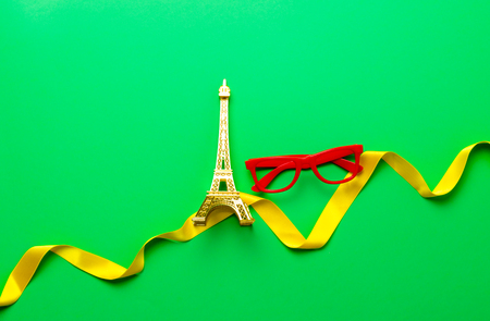Eiffel tower and glasses on green background