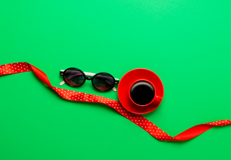 Cup of coffee and glasses with ribbon on green background