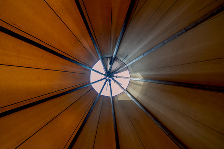 Looking up towards the smoke hole window teepee-ceiling from inside the tent shows bright day light filtering in creating a cozy ambience in the alternate lodging for glamping or outdoor adventurers Imagens