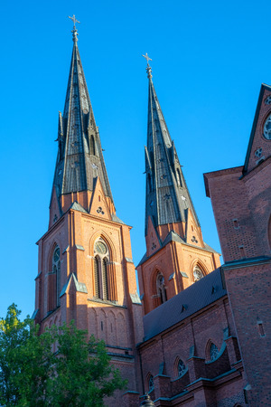 The twin towers, in french gothic style, of the Uppsala cathedral – halfway lit by the rising sun an early summer morning. The red brick facade of the tall building contrasting against a deep blue sky