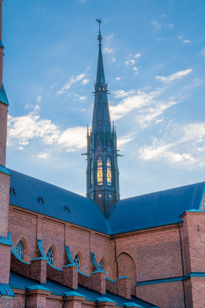 The transept tower of Uppsala cathedral an early summer morning. The lights not yet extinguished; a deep amber color is visible through the windows – it looks a little odd against the bright blue sky.
