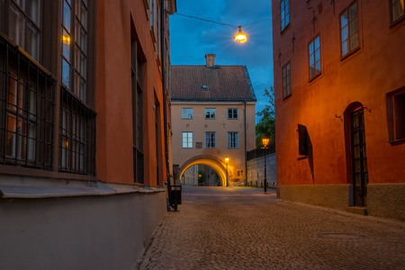 View of a small street or alley in the old town of the university city Uppsala, Sweden. It is almost midnight but the summer sky, a deep blue nuance, is still bright. Street lamps add deep amber light