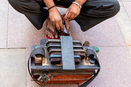 Indian shoemaker or cobbler in street workshop repairing shoes and other leather items. Reklamní fotografie