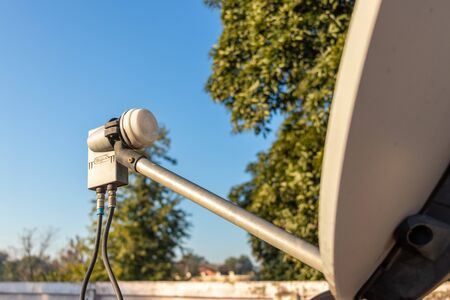 LNB, Satellite Dish over the blue sky in background, selective focus.