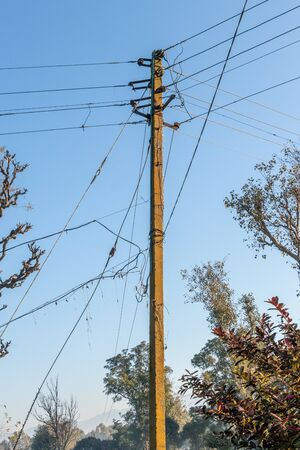 Concrete electrical three phase pole with messy wires