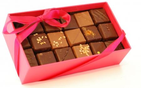 edibles: Casella rosa cioccolatini con nastro rosa su sfondo bianco. Archivio Fotografico