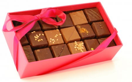 Pink box chocolates with pink ribbon on white background.