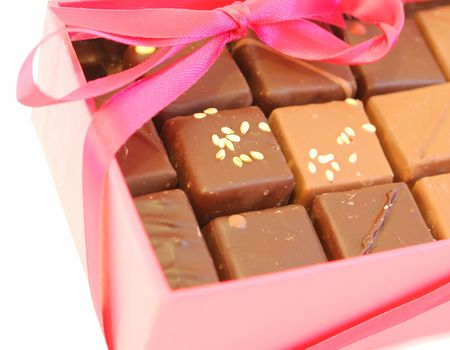 Pink box chocolates with pink ribbon on white background. photo