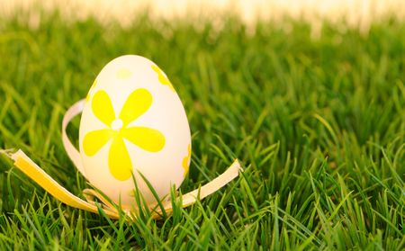 one isolated yellow painted easter egg against green background photo
