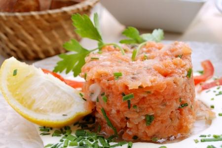 Tartare di salmone isolato sul piatto bianco, con limone.