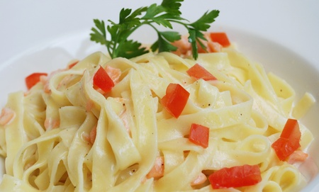 close-up of plate of pasta and smoked salmon with tomato  photo