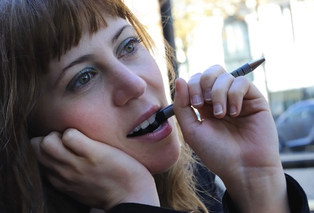 Outdoor portrait of young attractive urban woman thinking with a pen in mouth Stock Photo - 13236319