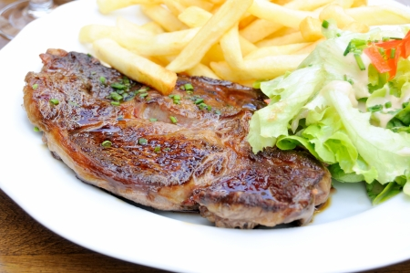 pork chop: isolated delicious and juicy pork chop with french fries and lettuce  Stock Photo