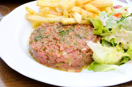 close-up of isolated classic steak tartare with lettuce on white plate  photo