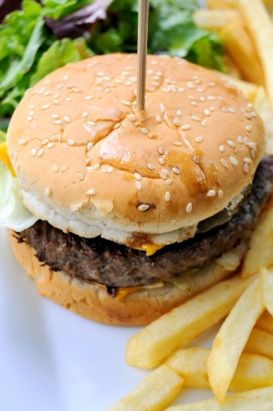 isolated delicious american cheese burger in table with french fries and lettuce in background photo