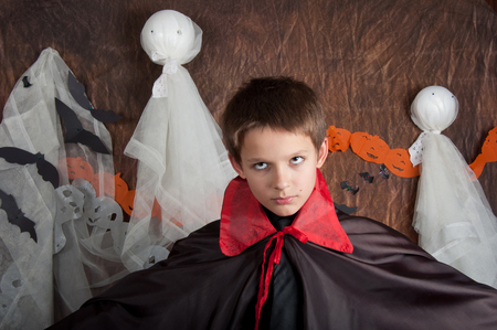 funny boy: Boy dressed like vampire for Halloween party. Brown background and white ghosts