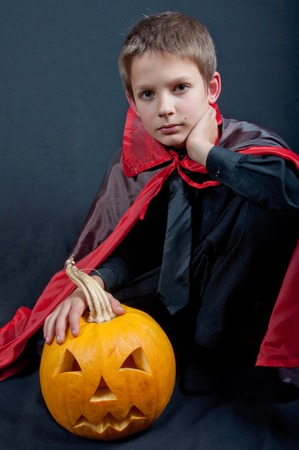 beautiful vampire: Boy dressed like vampire for Halloween party. Black and red clothes sitting near pumpkin, black background,