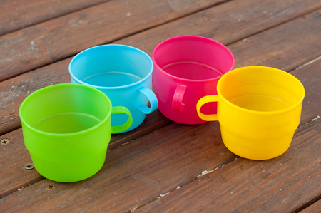 semicircle: Blue, pink, green and yellow cups staying semicircle on wooden table