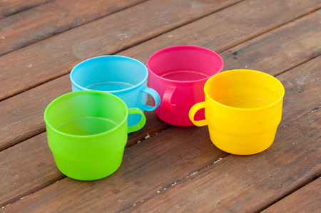 staying: Blue, pink, green and yellow cups staying semicircle on wooden table