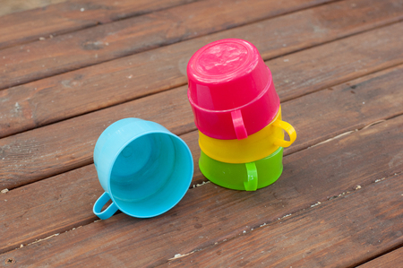 staying: Blue, pink, green and yellow cups staying on wooden table