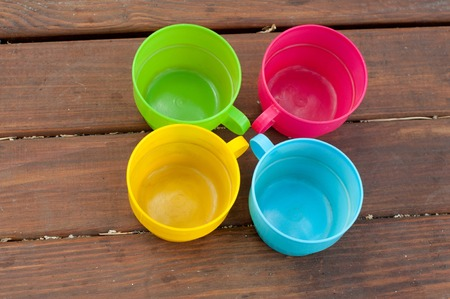 staying: Blue, pink, green and yellow cups staying circle on wooden table
