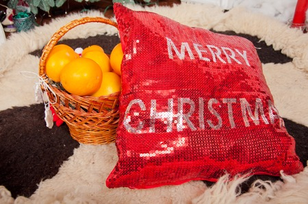 black carpet: Red christmas pillow and oranges in basket on white and black carpet