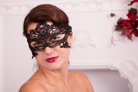 antifaz: Girl in black lace mask on white fireplace background with red flowers