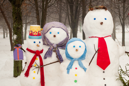 fun day: Family of  four snowmen outdoors in winter